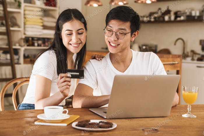 Image of happy couple holding credit card and using laptop