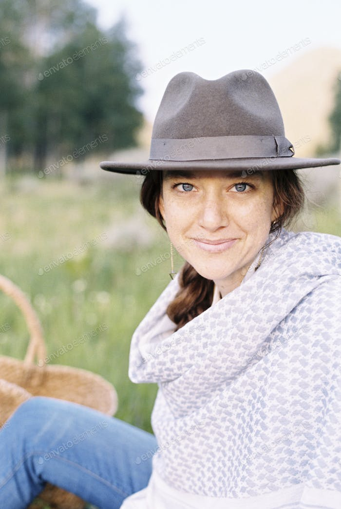 A woman in a hat and woollen shawl sitting in a meadow.