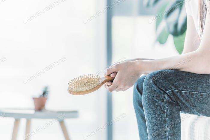 обрезанный выстрел молодой женщины держит расческу, сидя в помещении, концепция выпадения волос