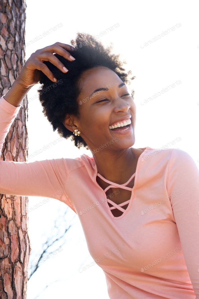Cheerful young black woman leaning on tree trunk