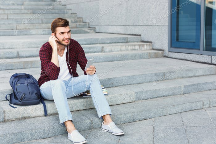 Student sitting on stairs and using smartphone