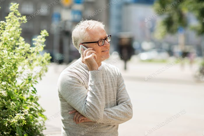 happy senior man calling on smartphone in city