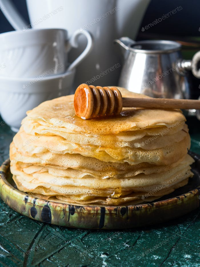 Stack of crepes with poured honey
