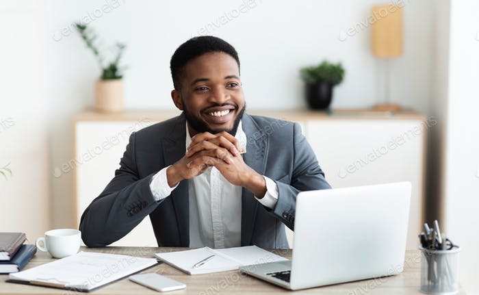 Smiling black businessman daydreaming at workplace in office