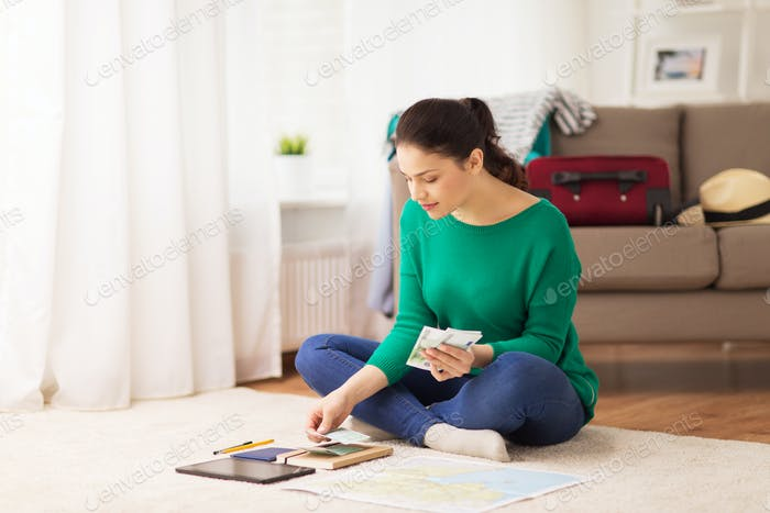happy woman with money and travel map at home