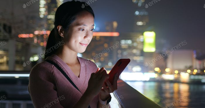 Woman use of smart phone in city at night
