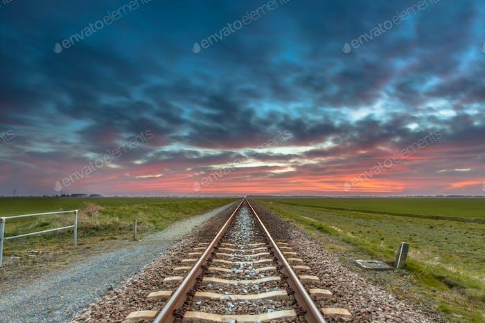 Endlose Eisenbahn in offener ländlicher Landschaft