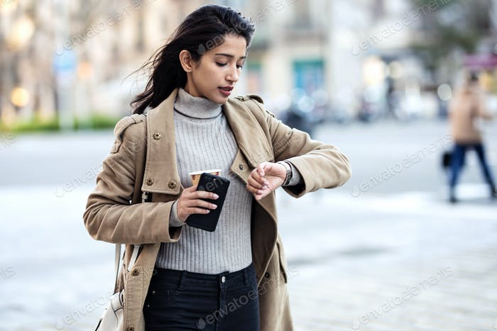 Shot of pretty young woman looking her watch while waiting a friend in the street.