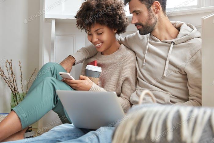 Chica afro positiva feliz de hacer compras en línea en cellualr, se sienta cerca del novio que trabaja en