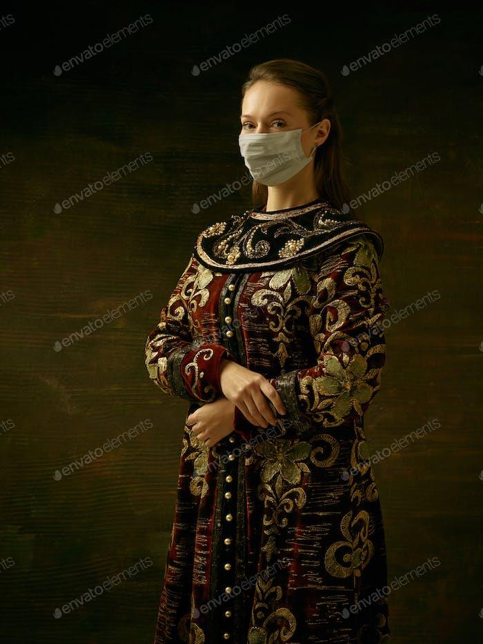 Mittelalterliche junge Frau als Herzogin trägt Schutzmaske gegen Coronavirus Verbreitung