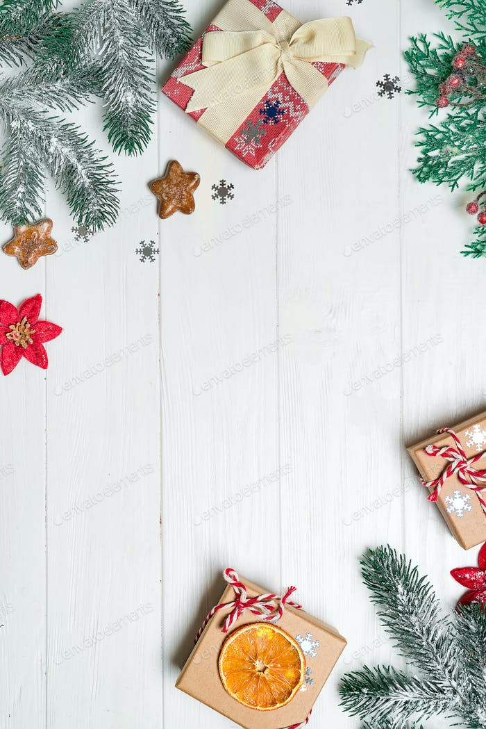 Christmas congratulation background with gifts, pine branches and Christmas ornaments on the wooden