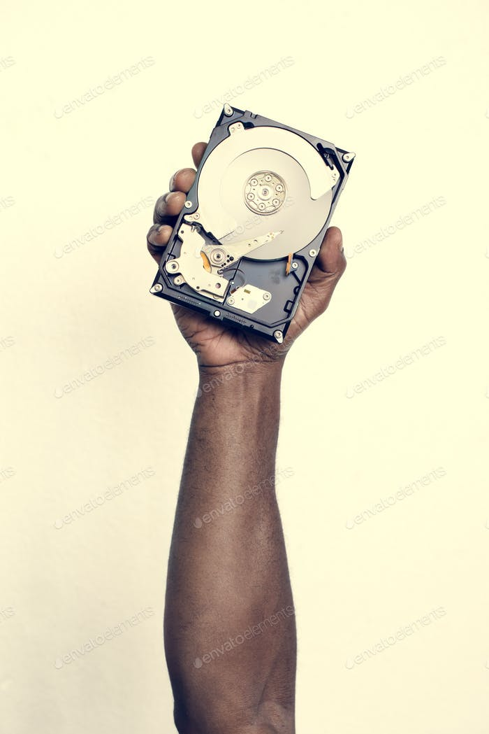 Hand holding hard disk drive isolated on background