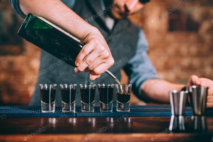 Portrait of professional barman pouring alcoholic digestif in shot glasses at bar