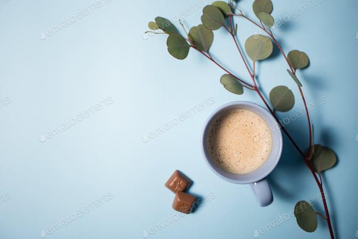 Café con chips de chocolate y rama de eucalipto sobre Fondo azul