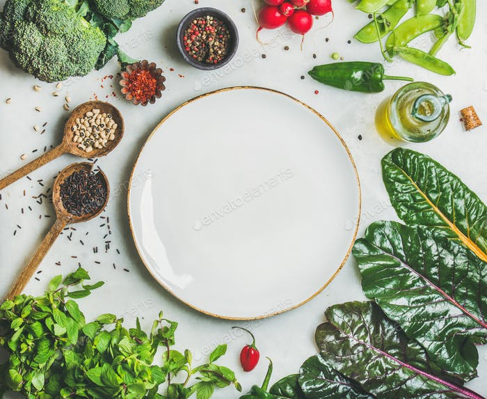 Healthy vegetables, greens and grains with white plate in center