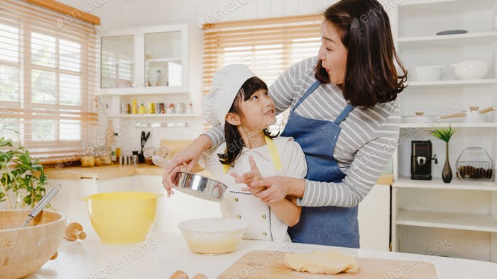 Asian family have fun cooking baking pastry or pie for breakfast meal in kitchen home in morning.