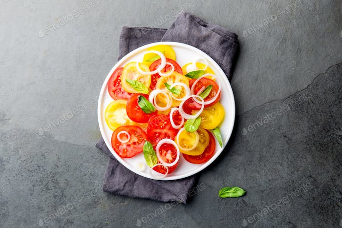 Red and yellow fresh tomato salad with onion, basil and olive oil on white plate. Gray slate
