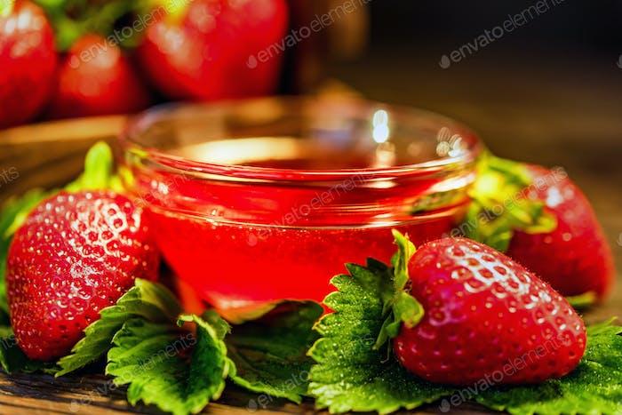 Frische Erdbeeren mit Blättern und Marmelade schließen