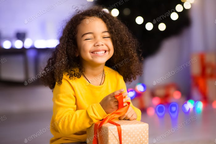 Happy african girl unwrapping her xmas gifts at home