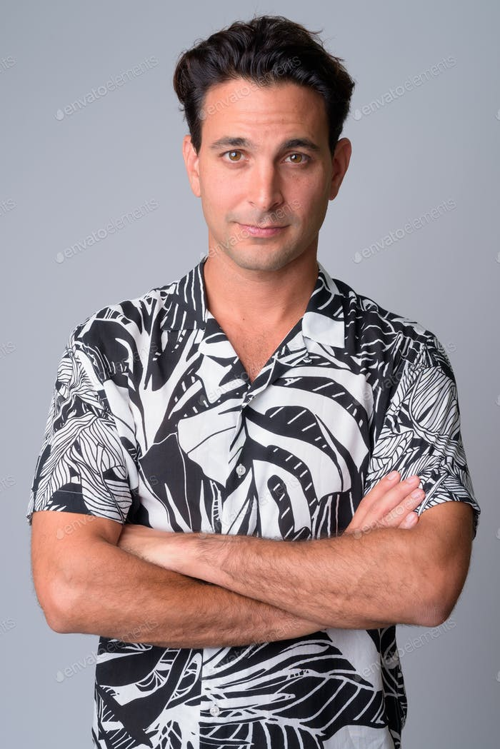 Portrait of handsome Hispanic tourist man with arms crossed