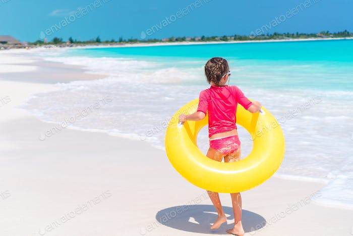 Adorable little girl having fun on the beach