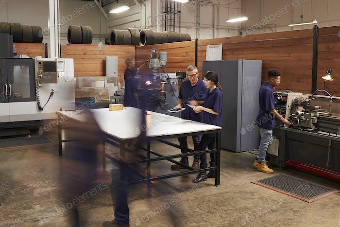 Engineers Working On Machines In Busy Metal Workshop