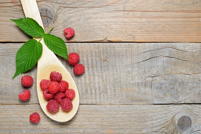 Raspberry in spoon on old wooden table