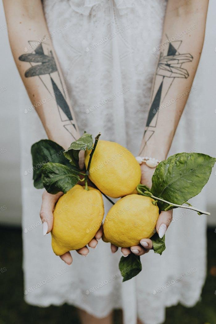 Tattooed hands holding fresh lemons