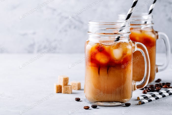 Iced coffee in glass mason jars with milk and ice cubes