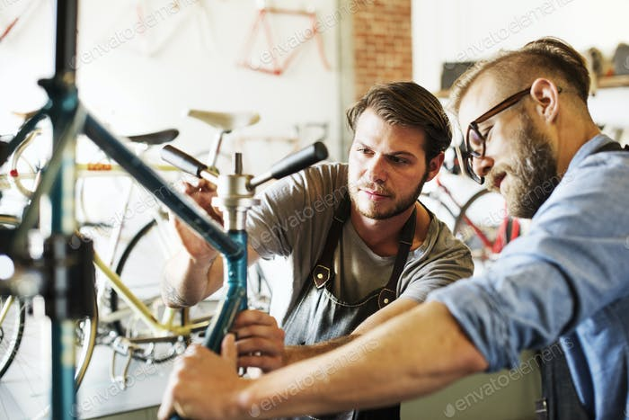 Two men in a cycle repair shop, looking at a bicycle.