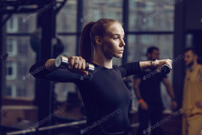 Slender young girl dressed in a black sportswear is doing exercises with dumbbells in the modern gym