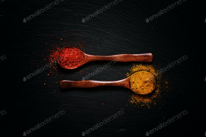Curry and chili pepper spices, wooden spoons, black stone background