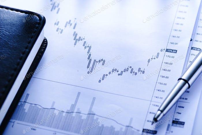 Journal mit Geschäftsdiagrammen und Stift öffnen