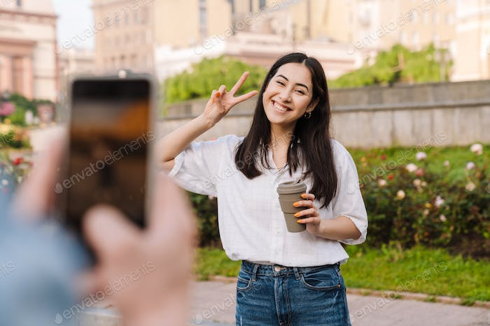 Image of couple taking on cellphone and gesturing peace sign