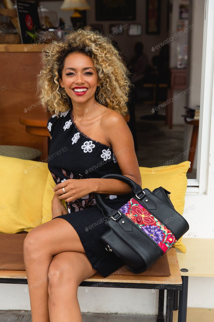 Attractive elegant African American lady with handbag on seat