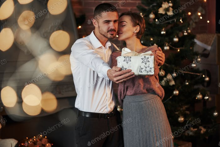 Christmas gift for the woman. Gentleman in classic suit gives his wife the present