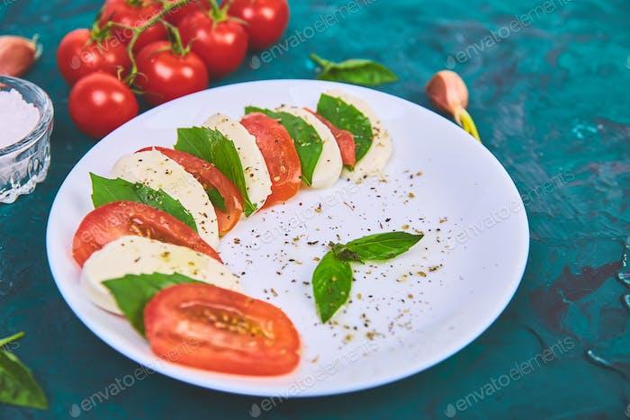 Italienischer Caprese-Salat mit Tomaten in Scheiben geschnitten, Mozzarella-Käse, Basilikum, Olivenöl.