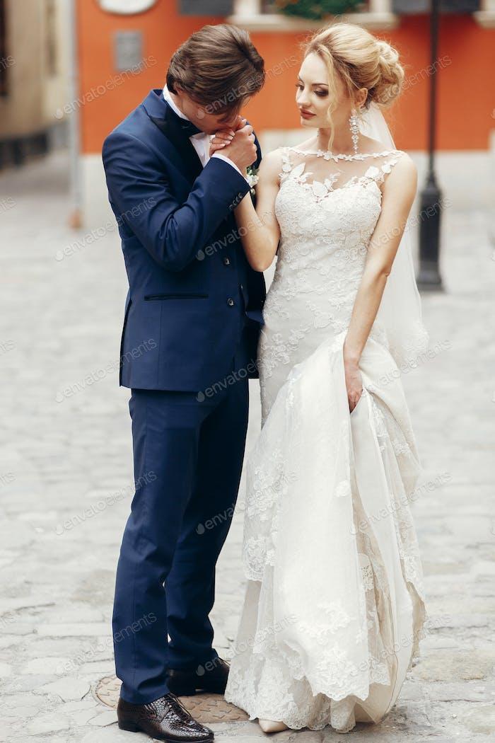 Newlywed bride and groom walking outdoors in wedding clothing