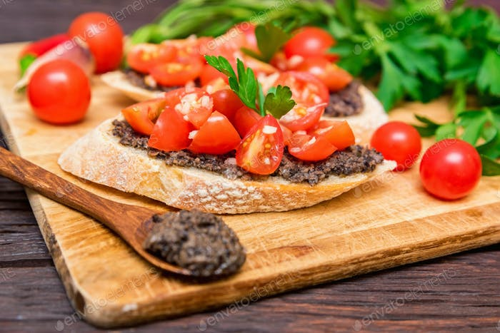 Fresh tasty bruschetta with truffle sauce, chili, parsley, tomates. Close view