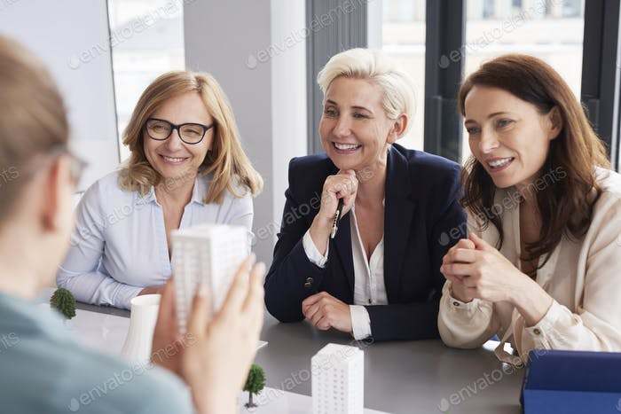 Three mature businesswomen having a conversation at conference table