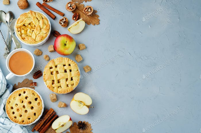 Grey stone background with apple pies, tea and nuts