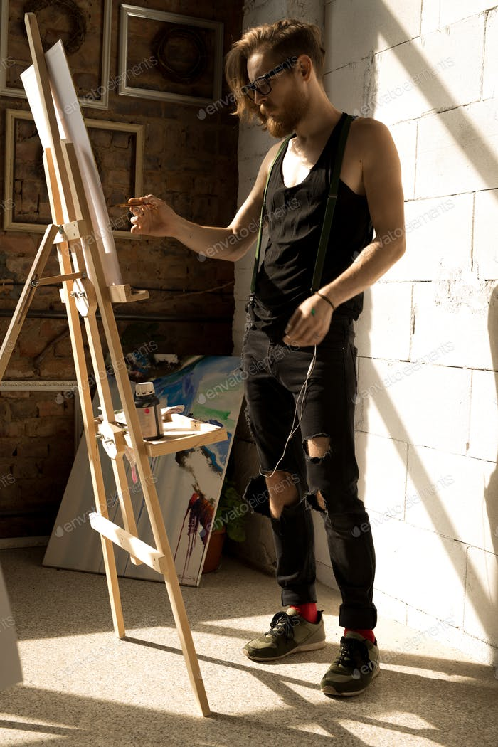 Inspired Male Artist Painting Picture on Easel