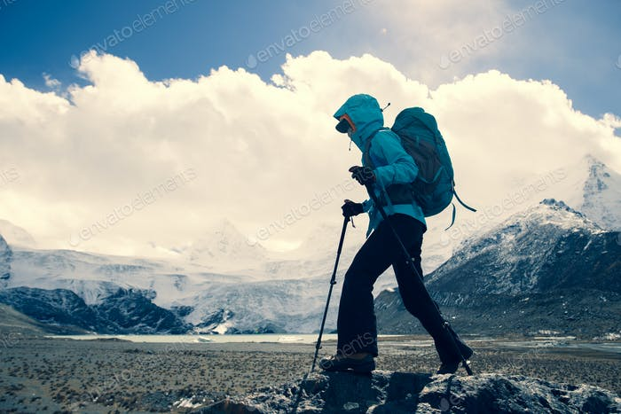 Woman hiker hiking in high altitude winter mountains