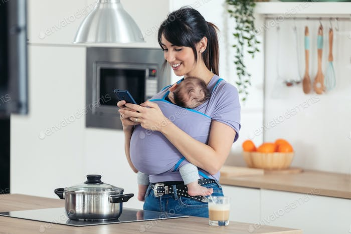 Pretty young mother with little baby in sling using her mobile phone in the kitchen at home.