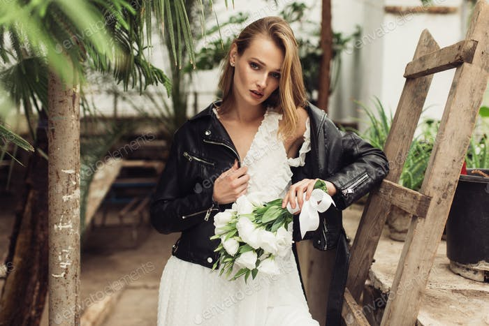 Young beautiful woman in black leather jacket and white dress ho