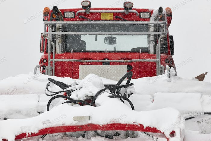 Snow blower truck covered by snow. Winter time. Snowing. Horizontal