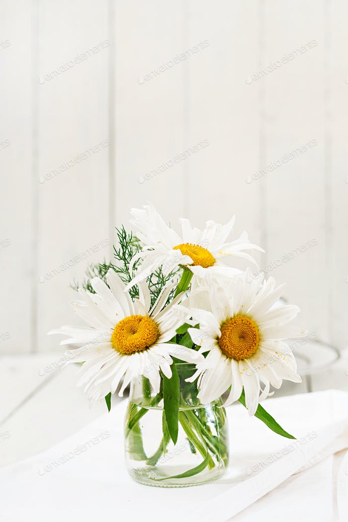 Bouquet of daisies in vase on a wooden white table