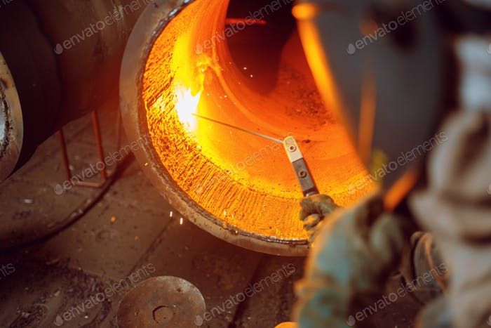 Welder works with metal on factory, welding skill