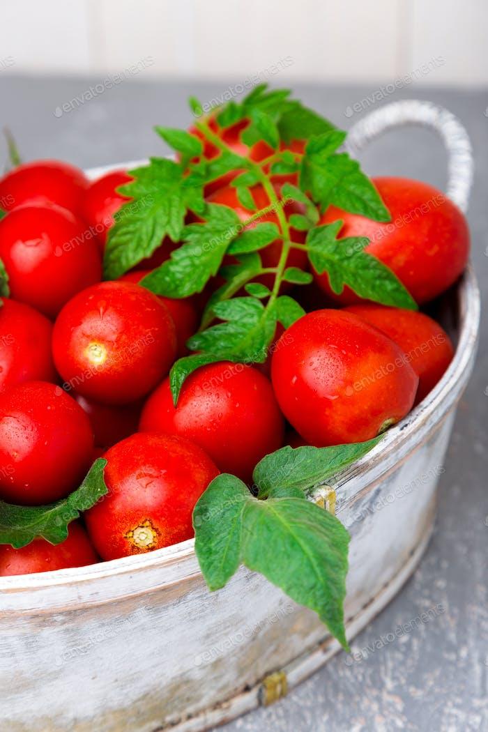 Rote Tomate in grauem Korb auf grauem Hintergrund. Ernte. Vollständige Schachtel Tomaten. Nahaufnahme.