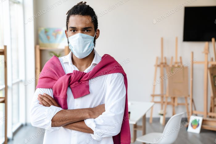 Young african american guy in face mask posing with arms crossed